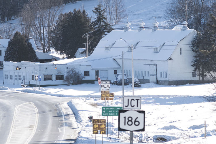 Looking down Route 86 towards Donnelly's Ice Cream and Farm on a cold December Morning Adirondacks Barns Cold Cold Temperature Dairy Direction Information Sign Lake Clear Perspective Road Road Sign Sign The Way Forward White Barn Winter