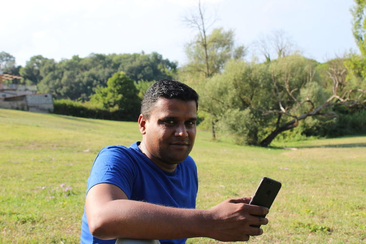 Portrait of young man using mobile phone on land