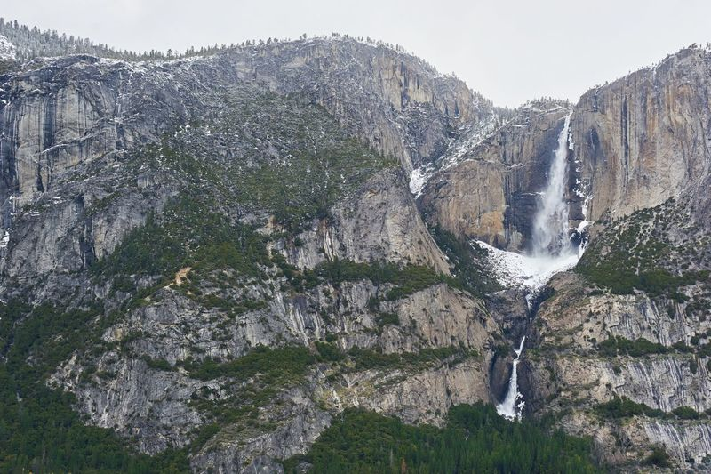 Scenic View Of Waterfall On Mountain Against Sky