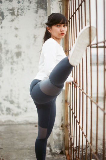 Side view of young woman standing by railing