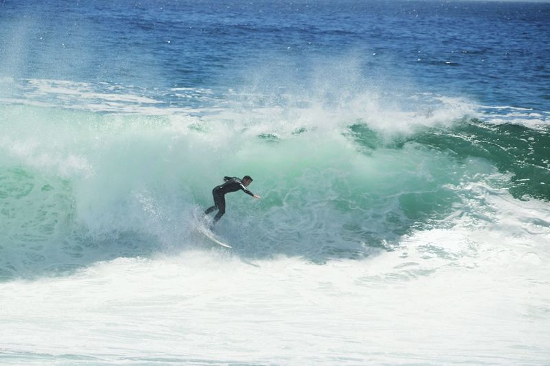Side view of man surfboarding on wave in sea