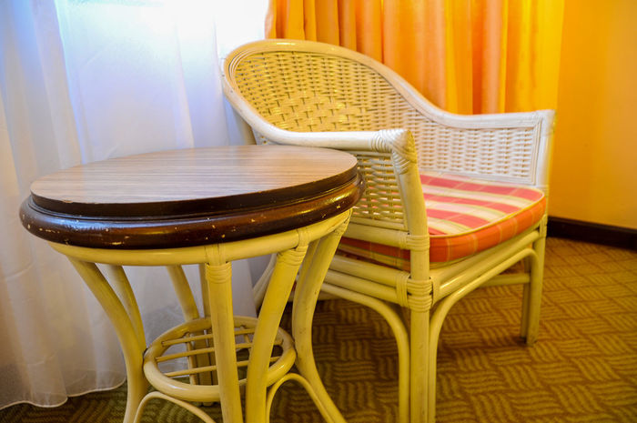Rattan chair and round table at the corner of hotel room Arm Chair Chair Curtain Day Hotel Hotel Room Indoors  Inside Hotel No People Rattan Chair Red Relaxing Round Table Sit Table