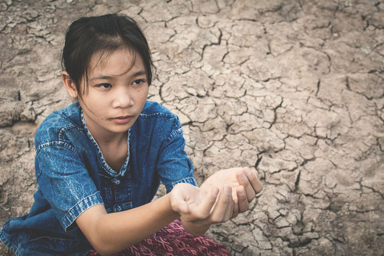 High Angle View Of Girl Sitting With Hands Cupped On Cracked Field