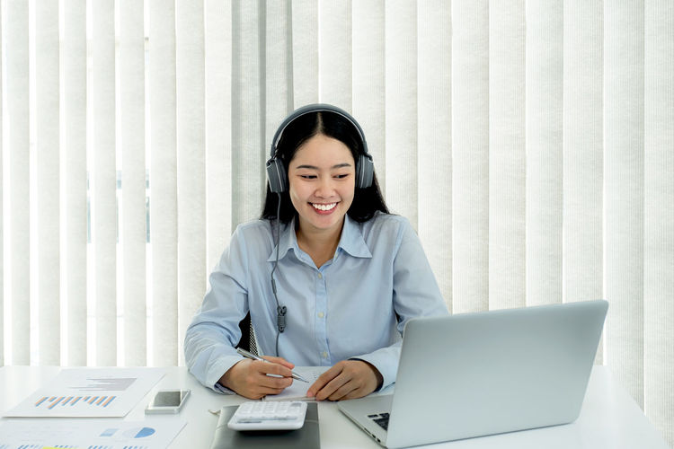 Smiling young woman using phone while sitting on table