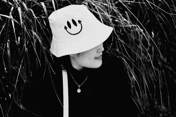 Portrait of woman with hat against plants