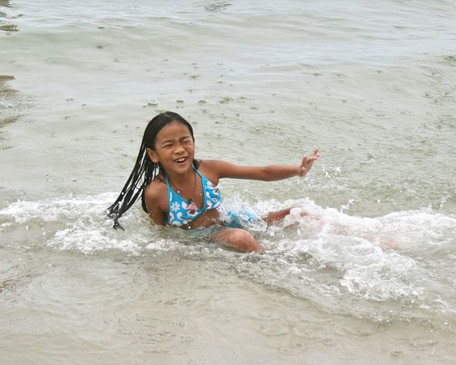 Cheerful teenage girl playing in sea