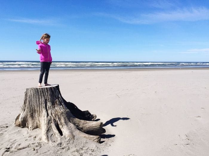 Full length of girl standing on tree stump at beach against sky