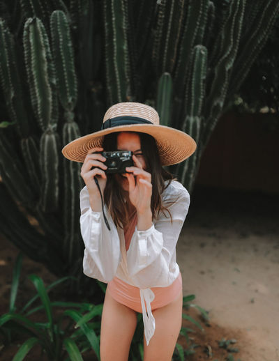 Girl taking pictures Hat One Person Real People Clothing Women Lifestyles Standing Young Adult Front View Fashion Sun Hat Hairstyle Girl Woman Fashion Beautiful Woman Brunette Camera Vintage Camera Taking Pictures Bathing Suit  Style Travel Summer Sri Lanka