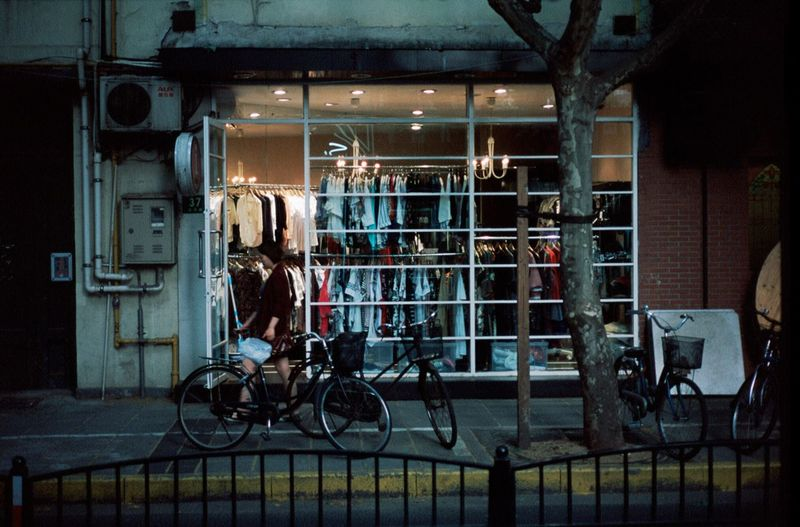 Bicycles on sidewalk against illuminated clothing store