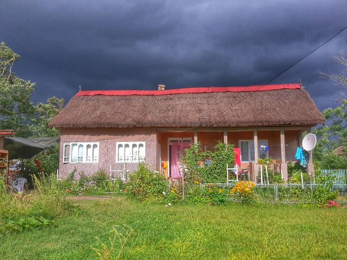 Houses on field against cloudy sky