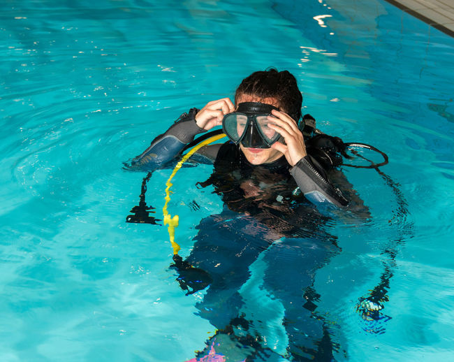 Young woman wearing swimming goggles in pool