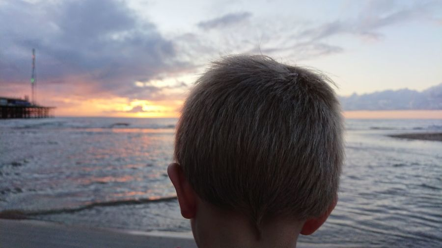 Close-up of boy at beach against sky during sunset