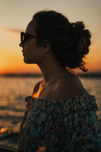 Young woman looking at sea against sky during sunset