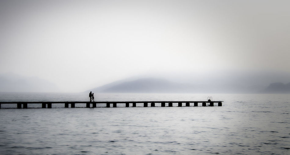 Silhouette people walking on pier over lake during foggy weather