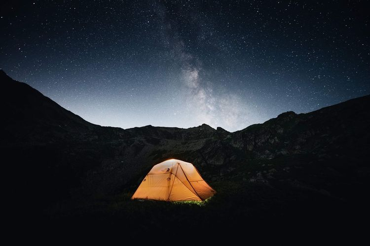 Tent on land against mountains at night