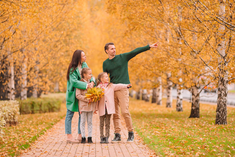Full length of father with arms raised during autumn