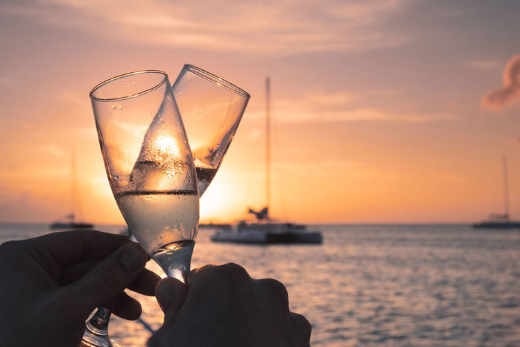 Drink Sunset Food And Drink Sky Refreshment Human Hand Hand Human Body Part Alcohol Drinking Glass Holding Sea Leisure Activity Real People Lifestyles Celebratory Toast Sun Outdoors Luxury Champagne Romance Boat Togetherness Copy Space Vacations