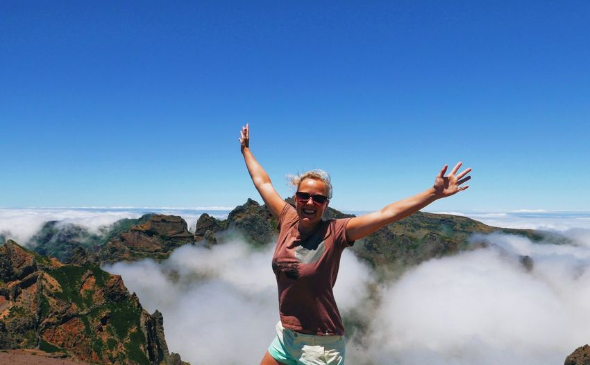 Excited woman with arms outstretched standing on cliff against clear sky