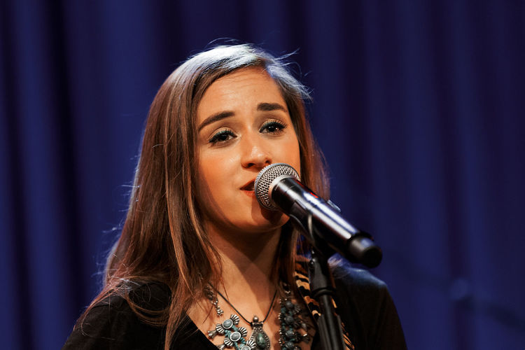 Close-up of young female singer performing on stage