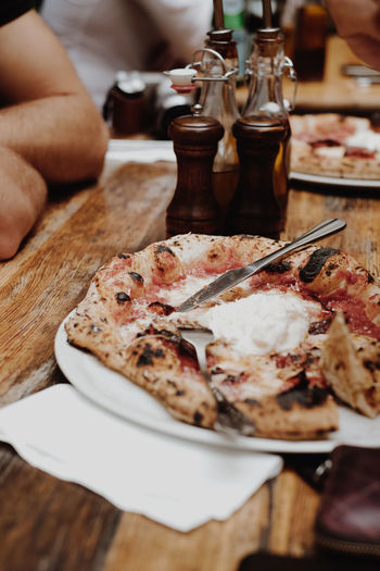 Close-up of hand by pizza on table
