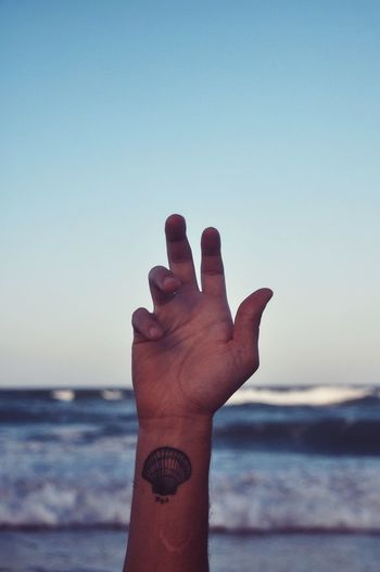 Close-up of human hand on beach