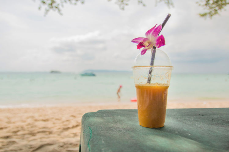 Close-up of drink on table at beach
