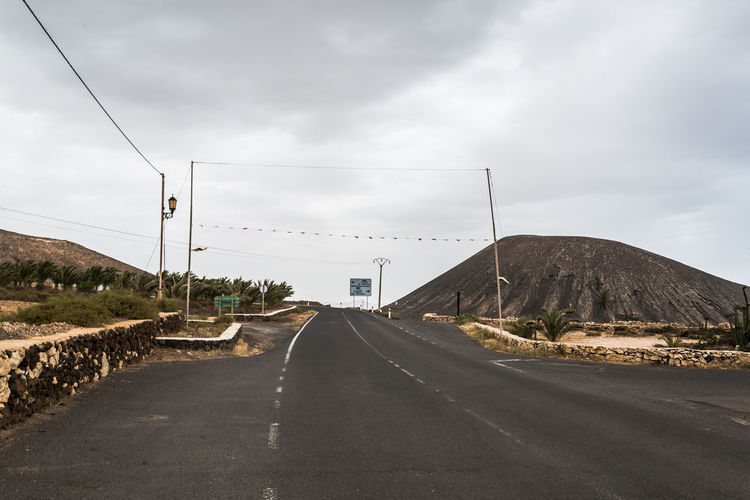 Canarias Colors Fuerteventura Cable Cloud - Sky Connection Country Road Day Diminishing Perspective Direction Electricity  Empty Road España Island Mountain Nature No People Outdoors Road Road Marking Sea Sign Sky Symbol The Way Forward Transportation vanishing point