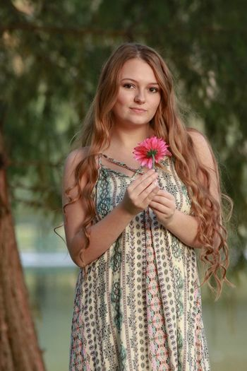 Portrait of beautiful young woman holding flower