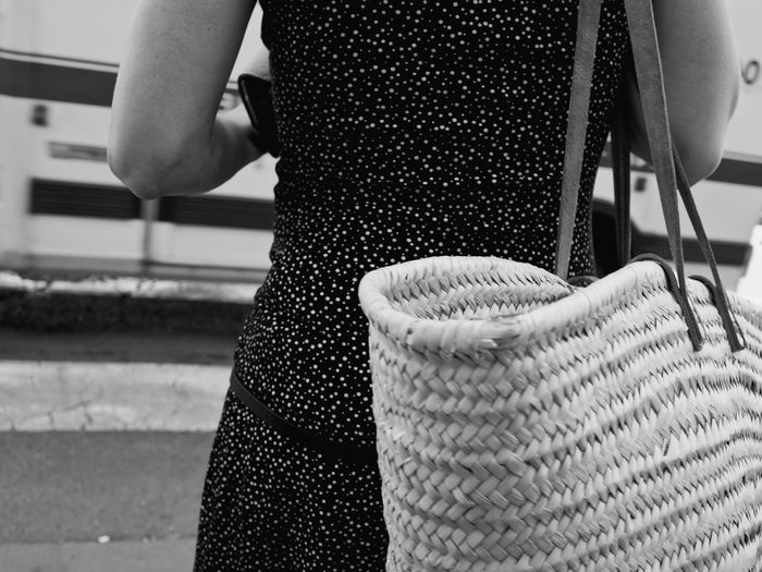 Rear view of woman carrying wicker bag