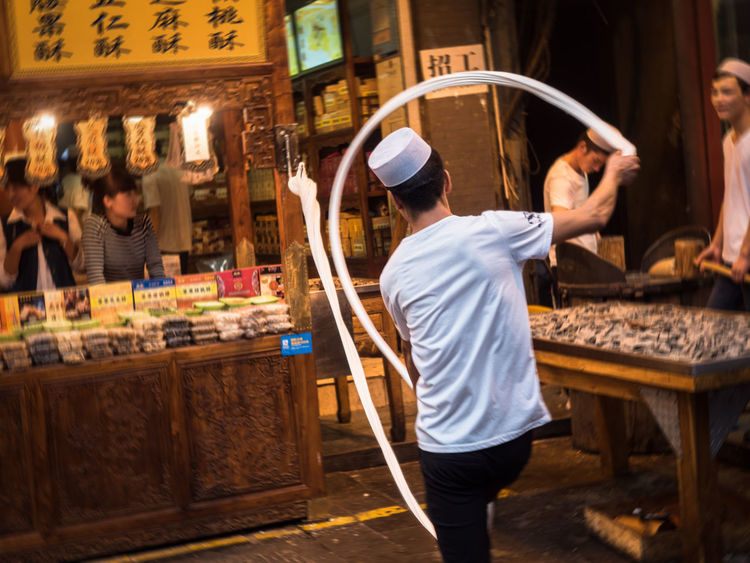A muslim in Xi'an kneading Tang, a pastry form of sugar. The dough is pulled and swung from a hook. Action Action Shot  China Hard Work Motion Blur Muslim Culture Occupation Street Photography Suga Taking Photos Travel Destinations Travel Photography Work The Photojournalist - 2017 EyeEm Awards