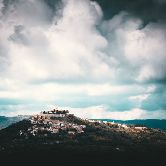 """The small historical village Motovun in central Istria is situated on a hill 270 meters m a.s.l. At the time of the Romans the settlement called """"Montana"""" - as it is still called in Italian today. Location: Motovun, Croatia Equipment: Fujifilm X-H1 + XF16-55 F2.8. Cloud - Sky Sky Architecture Building Exterior Nature Built Structure Day Building No People Scenics - Nature Mountain Beauty In Nature Outdoors City Tranquility Environment Landscape Residential District Tranquil Scene Motovun Croatia Hill Town EyeEm Best Shots Fortress"""
