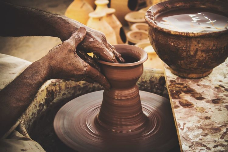 Cropped Image Of Hands Making Earthen Pots On Wheel At Workshop