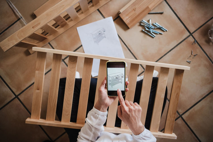High angle view of woman using smart phone on table
