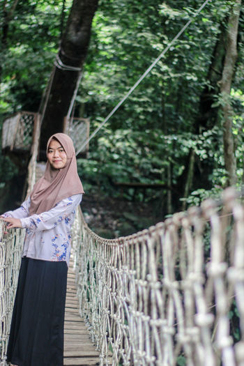 Portrait of woman wearing hijab standing on rope bridge against trees in forest