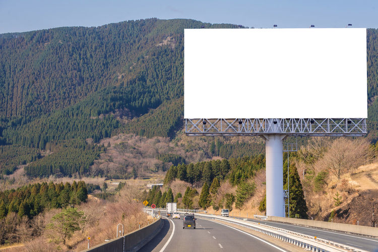 Billboard Blank Communication Copy Space Day Direction Highway Marking Motor Vehicle Mountain Nature No People Outdoors Plant Road Road Marking Road Sign Sign Symbol The Way Forward Transportation Tree