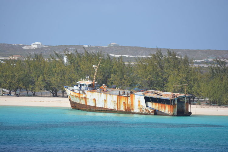 View of obsolete ship near beach against clear sky
