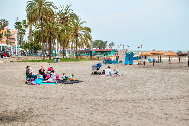 Malaga, Spain - April 21, 2018. Family at the beach, Malaga city, Spain Family Fun Kids Palm Tree Relaxing SPAIN X-M1 Beach Clear Sky Costa Del Sol Crowd Day Fuji Fujifilm Group Of People Holiday Land Large Group Of People Leisure Activity Men Nature Outdoors Palm Tree Plaing Plant Real People Roberto Sorin Sand Sky Tree Trip Tropical Climate Vacations Adventures In The City The Street Photographer - 2018 EyeEm Awards The Photojournalist - 2018 EyeEm Awards