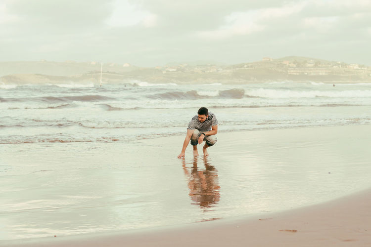 Rear view of father with son on beach