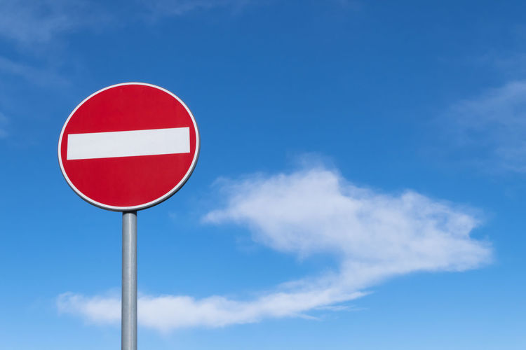 Low angle view of road sign against blue sky