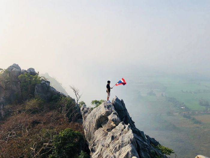 High angle view of man holding thai flag while standing on rock