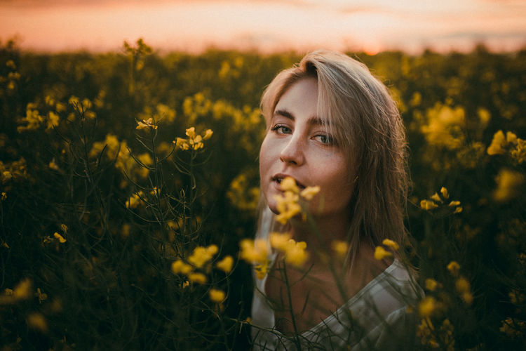 Portrait of young woman with yellow flowers on field