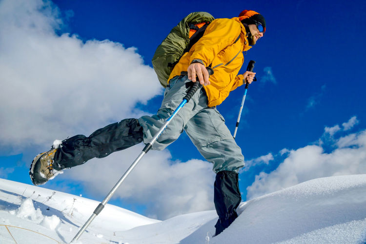 Low angle view of man hiking on snow against sky