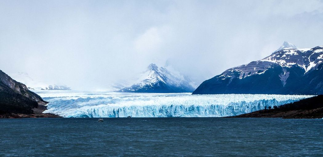 Idyllic Shot Of Perito Moreno Glacier And Mountains In Sea Against Cloudy Sky