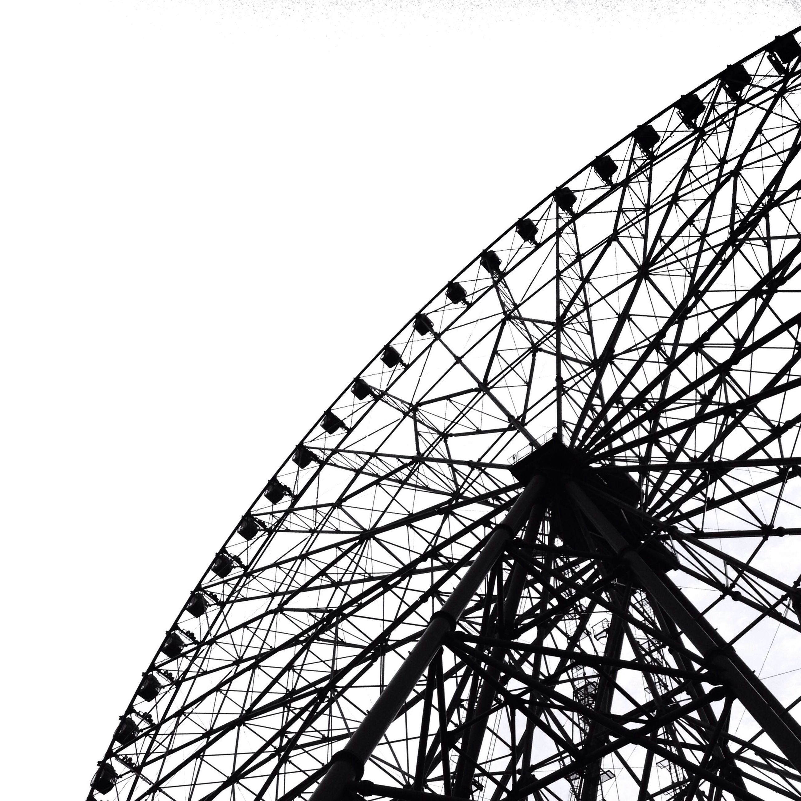 low angle view, clear sky, metal, ferris wheel, amusement park ride, metallic, amusement park, built structure, architecture, arts culture and entertainment, sky, silhouette, engineering, grid, no people, day, outdoors, tall - high, connection, tower