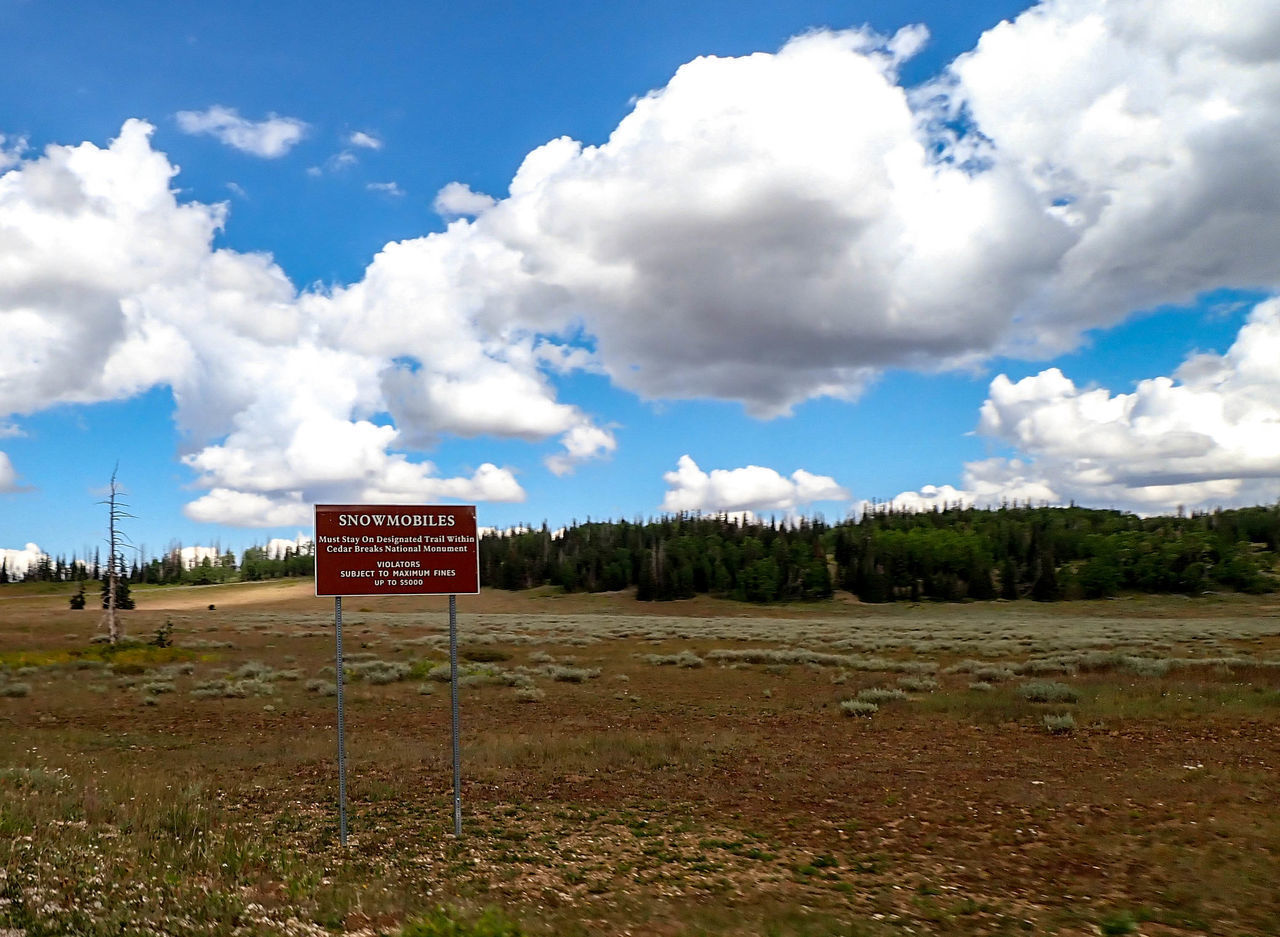 cloud - sky, sky, communication, sign, text, western script, land, nature, landscape, field, no people, environment, plant, day, information, tranquility, information sign, beauty in nature, tranquil scene, grass, outdoors