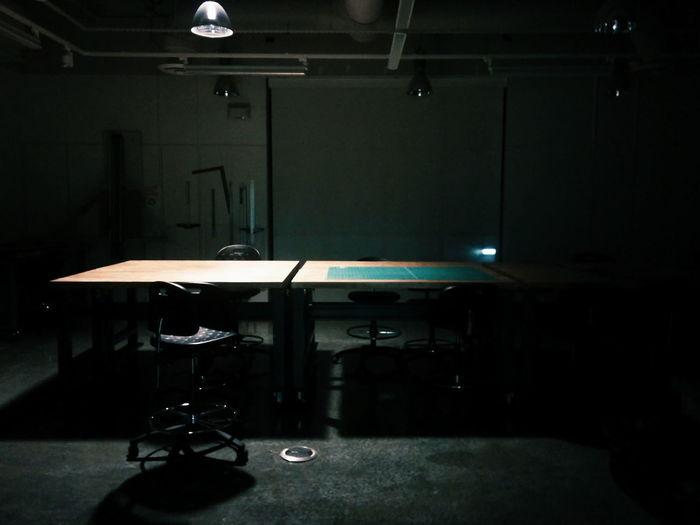 Single light shining on large desk and single desk chair Single Light Source Moody Large Desk