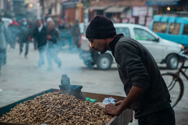 Side view of young man selling peanuts on street in city