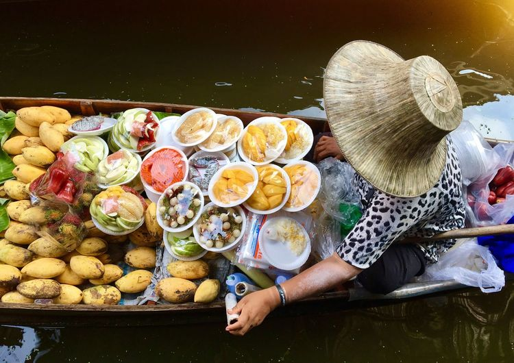 High angle view of woman selling food in boat on lake
