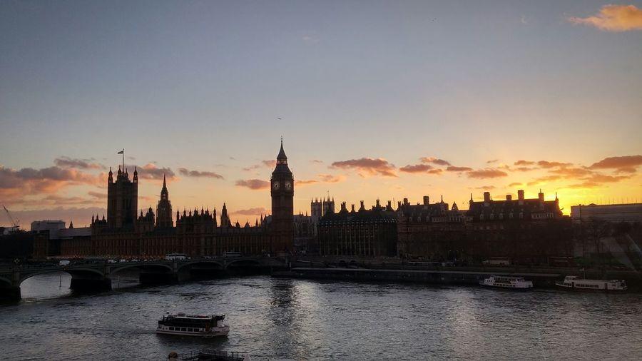 Westminster bridge over thames river by big ben against sky during sunset