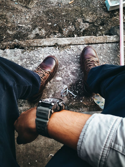 Low section of man wearing shoes and wristwatch on steps